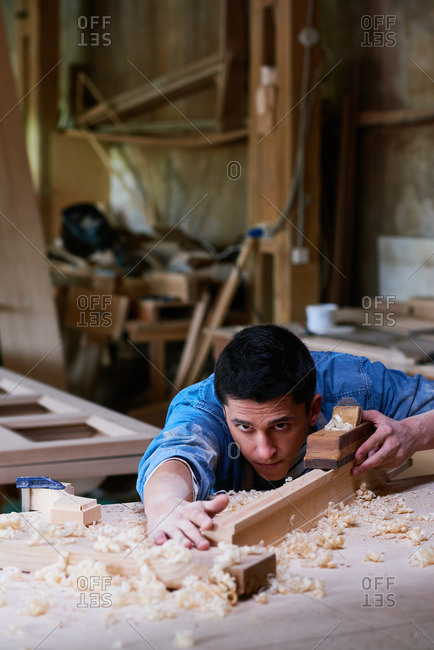 Craftsman checking out his work with a wood plane in his workshop