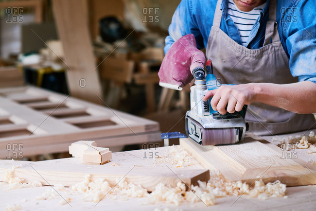Close up of a craftsman using a belt sander in his workshop