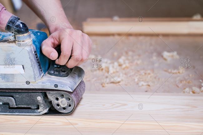 Close up of a man using a belt sander