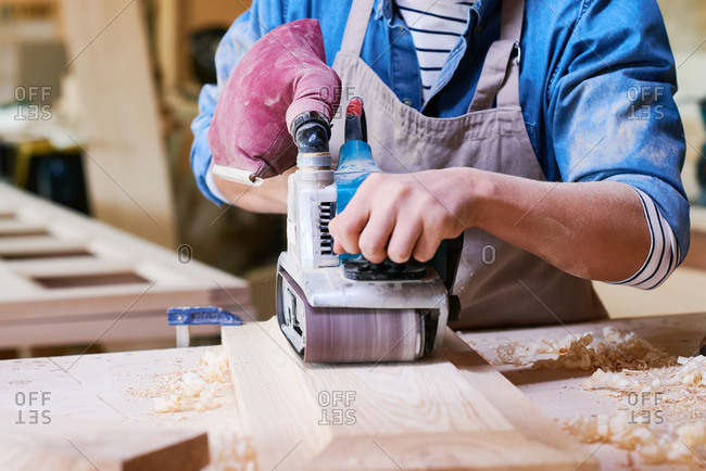 Close up of man using a belt sander in his workshop