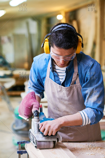 Man wearing ear protection and safety glasses while using a belt sander in his workshop
