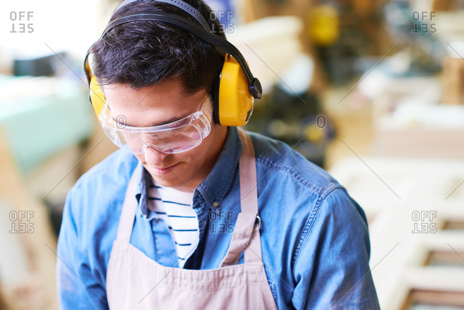 Close up of a craftsman wearing ear protection and safety glasses
