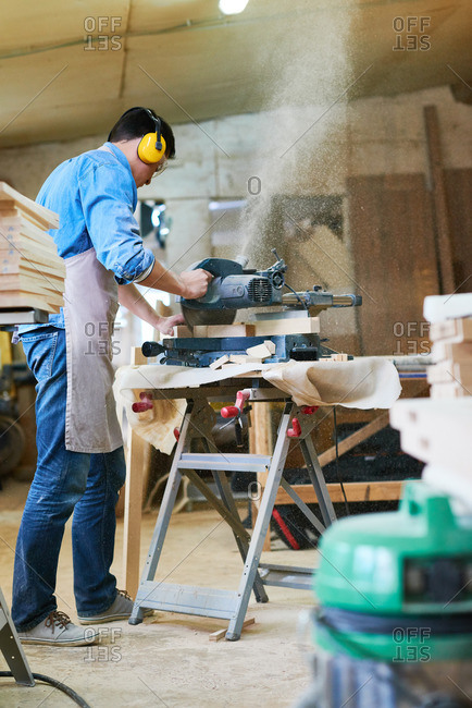 Man using a miter saw to saw wood in his workshop