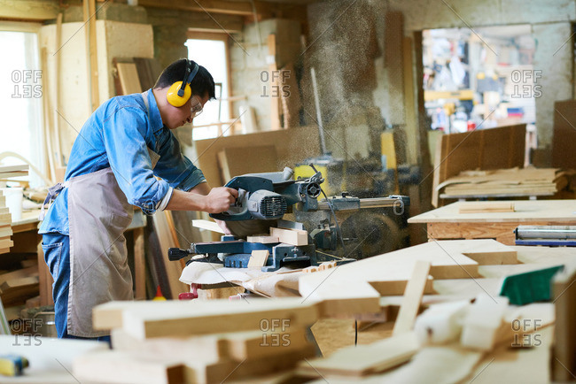 Man using a miter saw to cut wood in his workshop