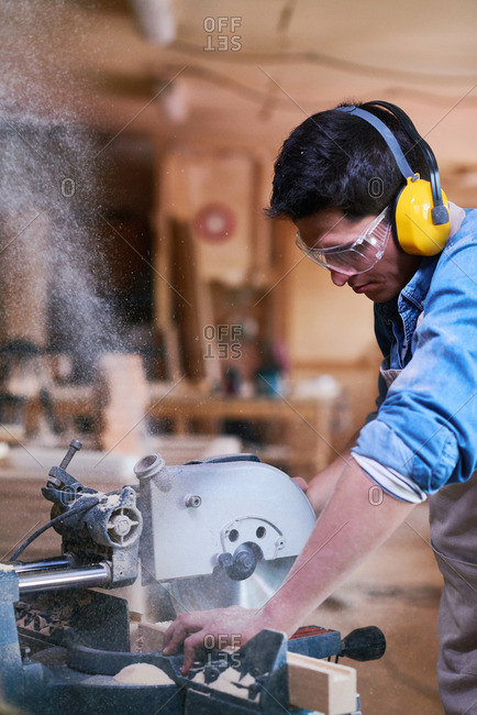 Man cutting wood with a miter saw in his workshop