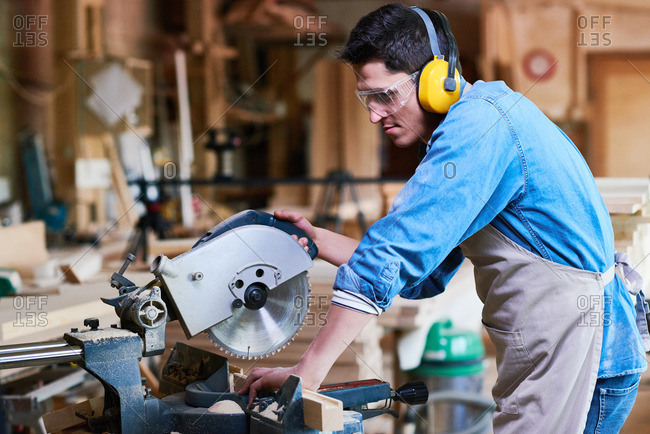 Man using a miter saw in his workshop
