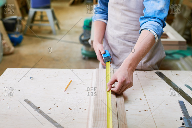 Close up of a man using a tape measure to measure the length of a board in his workshop