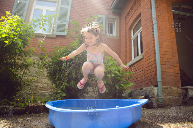 Girl leaping into kiddie pool