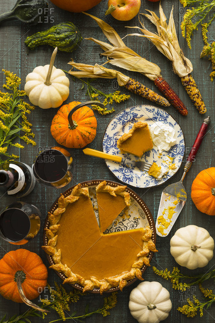 Pumpkin pie served among small pumpkins and Indian corn