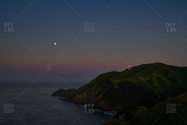 Scenic view of a rocky headland at dusk