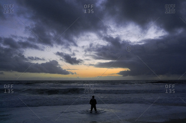 Silhouette of person standing in the ocean