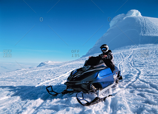 Man driving snowmobile over hill