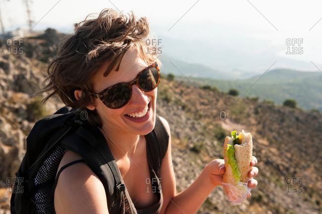 Hiker eating sandwich on hill
