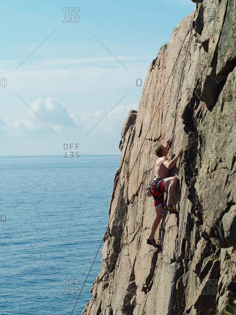 Man scaling coastal rock wall