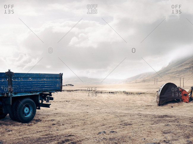 Blue truck and digger in dry field