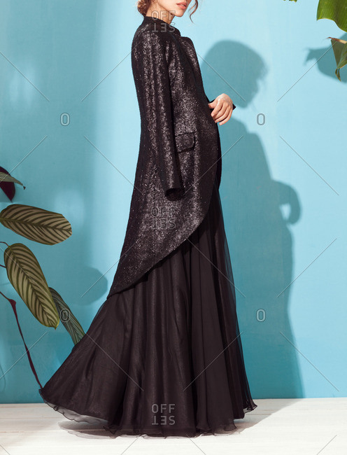 Young model wearing black dress and sequined jacket