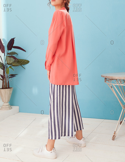 Young model wearing a pink blouse and striped culottes