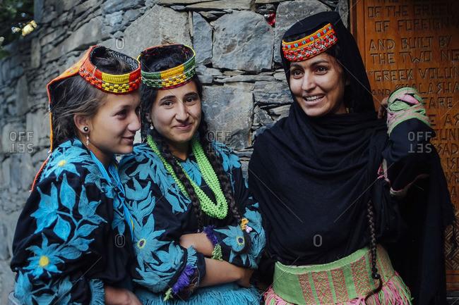 Chitral, Pakistan - May 20, 2016: Kalash teenagers smile outside house