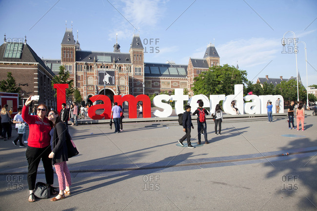 Amsterdam, Netherlands - June 1, 2016: Tourists taking selfie in front of sign at the Stedelijk Museum