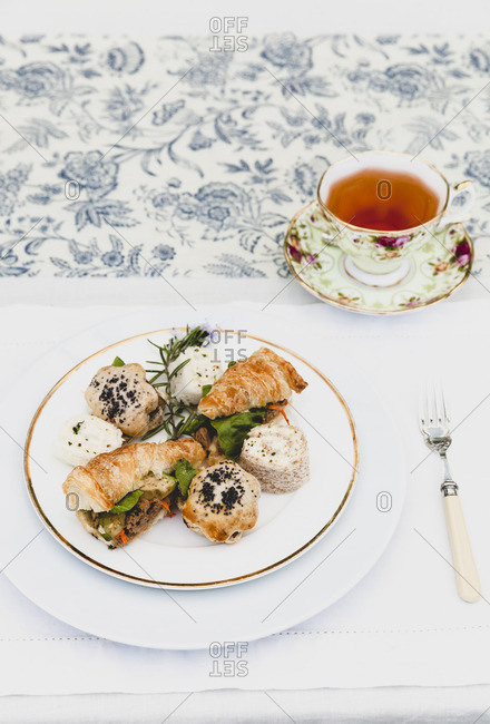 Teacup and finger sandwiches on tablecloth