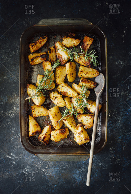 Overhead view of roasted potatoes in a pan with rosemary and wooden spoon