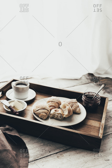 Croissants with coffee on a wooden tray