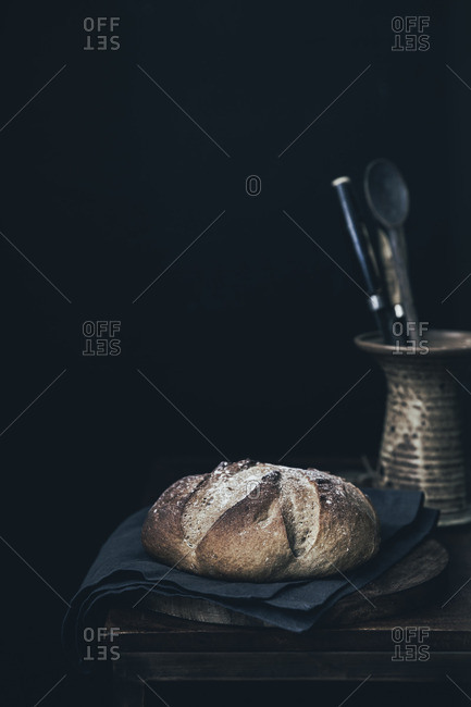 Rustic boule on wooden table with utensils