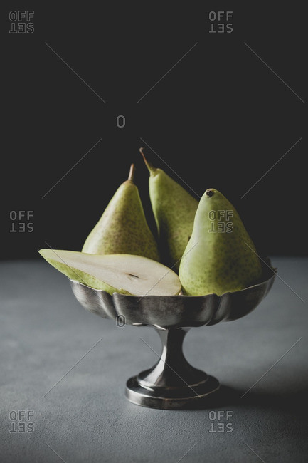 Still life of pears in tarnished silver bowl