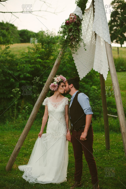 Bride and groom kissing under wooden posts