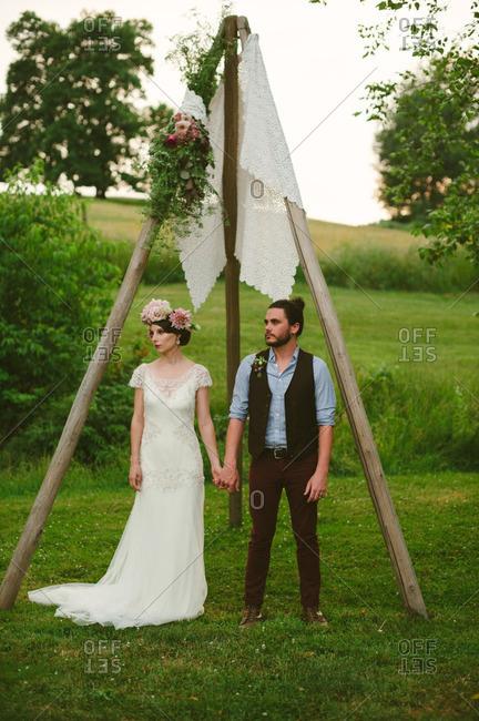 Bride and groom standing under wooden posts