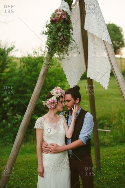 Bride and groom embraced under wooden arbor