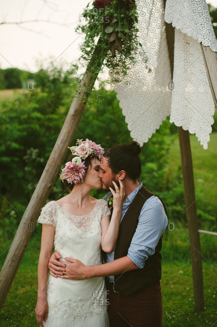 Bride and groom kissing under wooden arbor