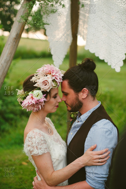 Close up of bride and groom kissing under wooden arbor