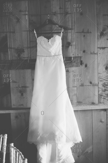 Wedding gown hanging on wooden wall in black and white