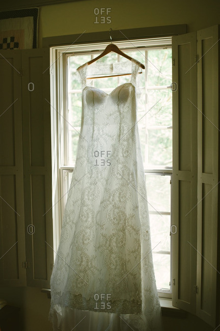 White wedding gown hanging in front of a window