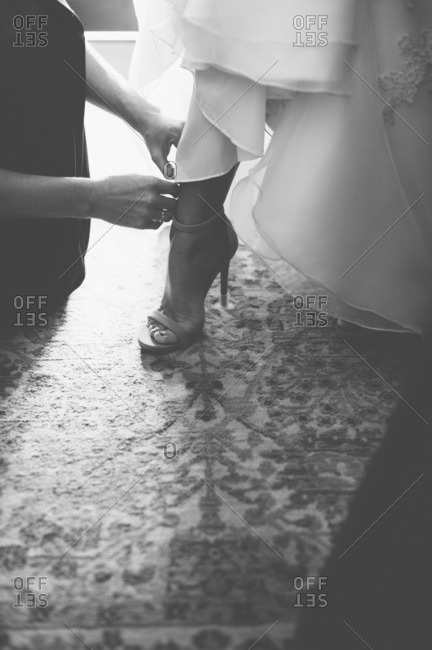 Bridesmaid helping bride put on her high heels