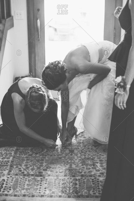 Bridesmaid helping bride put on her shoes