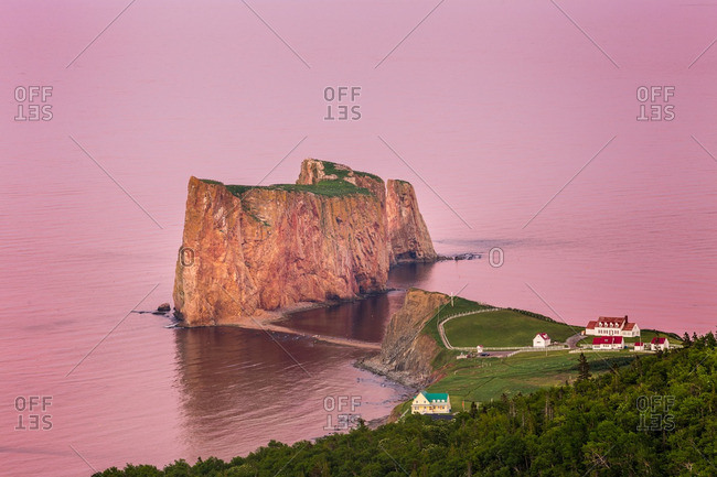 Perce Rock in pink sunset light from afar