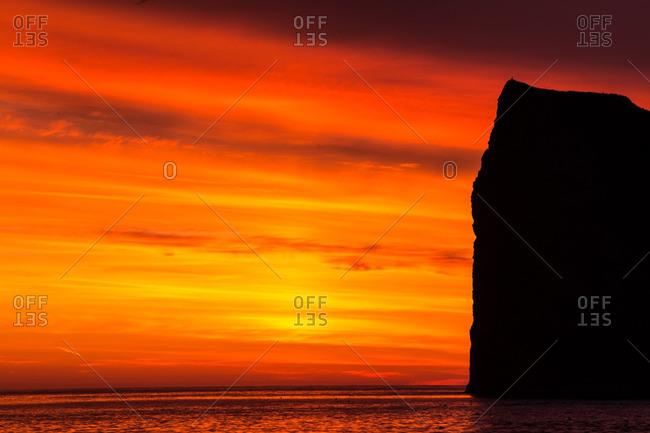 Perce Rock silhouette in orange sunrise light