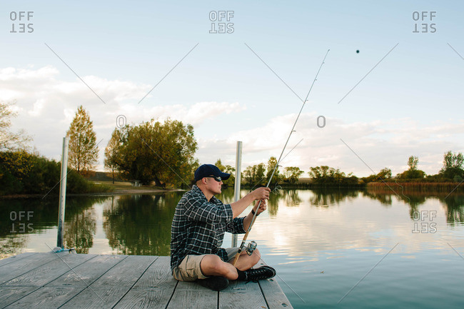 A man alone fishing on dock