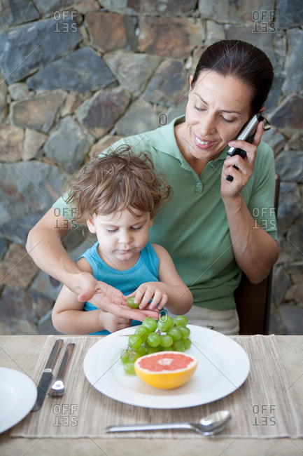 Woman eating breakfast with son