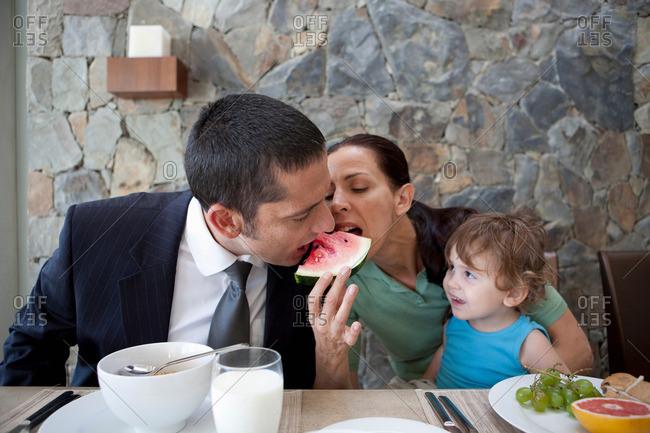 Couple sharing watermelon at breakfast