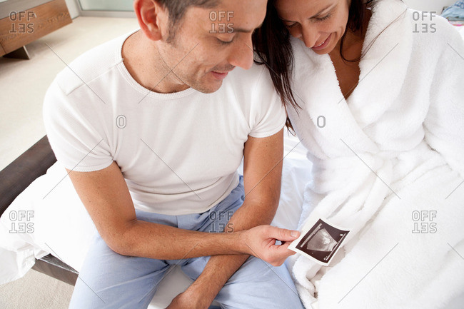 Couple examining sonogram together - Offset
