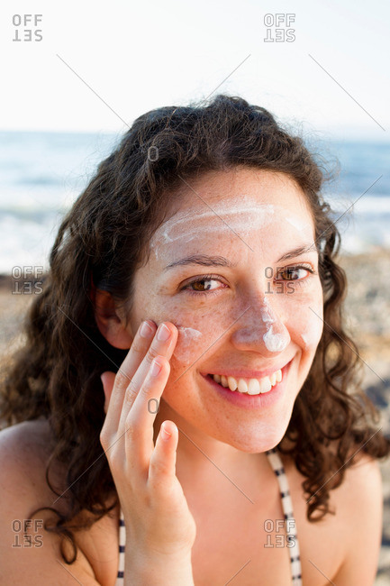 Smiling woman applying sunscreen to face