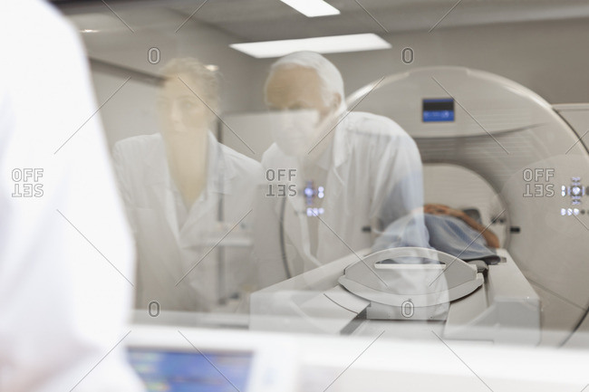 Doctors operating CT scanner in hospital