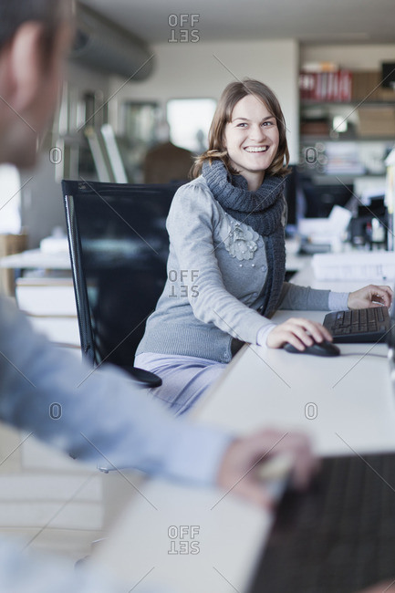 Smiling businesswoman talking at desk