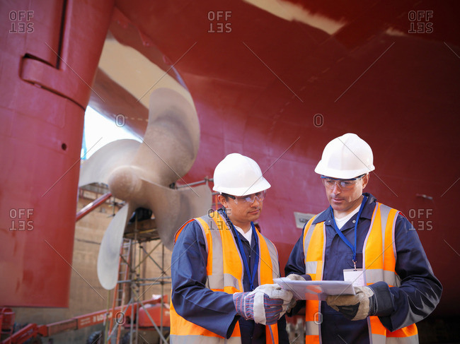 Workers next to underside of ship in dry dock