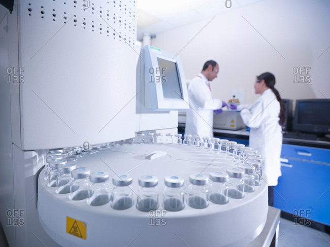 Scientists in laboratory with analytical scientific equipment
