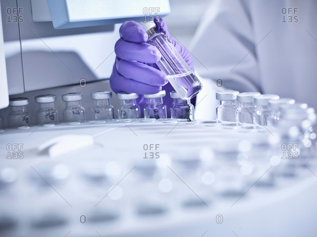 Scientist holding sample in laboratory with analytical scientific equipment