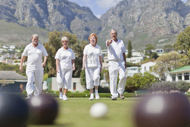Older couples lawn bowling - Offset
